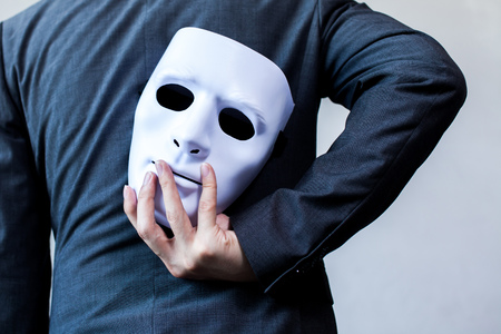 Photo for Business man carrying white mask to his body indicating Business fraud and faking business partnership. - Royalty Free Image