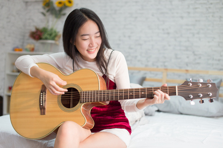 Photo pour Cute and happy smiling Asian girl playing acoustic guitar in bedroom - image libre de droit