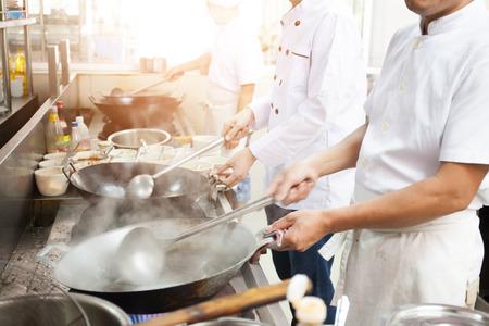 Foto de Group of chefs in hotel or restaurant kitchen busy cooking - Imagen libre de derechos