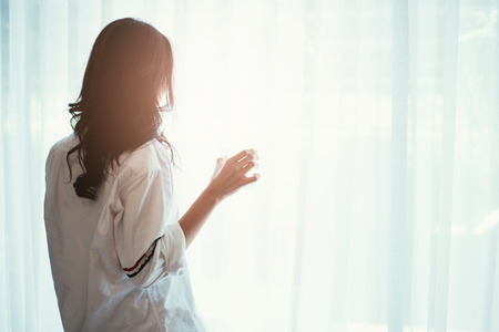 Foto de Woman holding a glass of water while looking out of the window - back of silhouette woman - Imagen libre de derechos