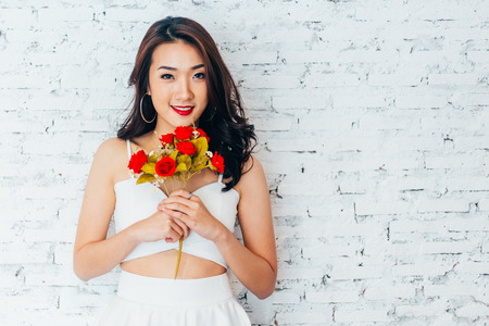 Photo for Young happy Asian woman smiling in fashionable dress and holding bouquet of roses over white wall background - Royalty Free Image