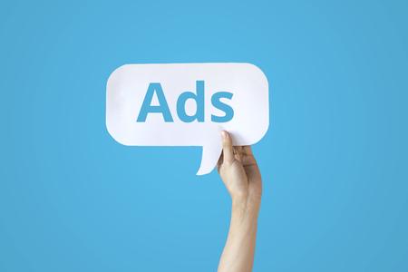 Foto de Human hands holding a bubble speech of word 'Ads' in all blue background - Imagen libre de derechos