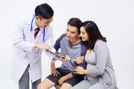 Photo for Gynecologist or Obstetrician Physician showing ultrasound photo to a couple of pregnant woman and husband - Royalty Free Image