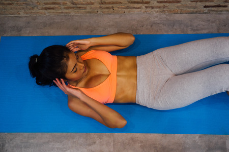 Photo for Young sporty muscular woman lying on exercise mat performing sit-ups. Top view of woman in sport clothing doing abs crunches in vintage gym - Royalty Free Image