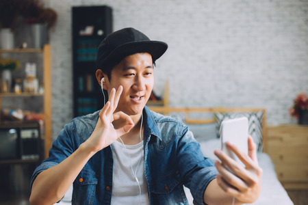 Photo for Young happy Asian man talking video call via smartphone wearing headphones at home - Royalty Free Image