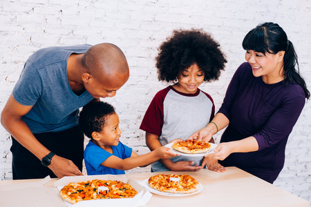 Photo pour Happy family of African American parents and little boy and girl having pizza together happily at home. Family and parenthood concept - image libre de droit