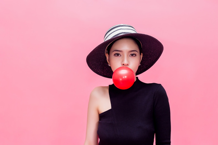 Foto de Young sweet and attractive woman in luxury fashion lifestyle blowing chewing bubblegum isolated over pink background - Imagen libre de derechos