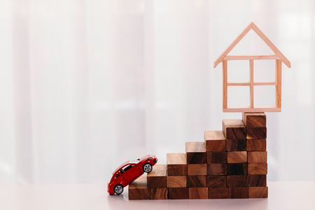 Photo pour Toy car driving up towards the stairs of achievement with house on the top - big dream and growth achievement in buying house and property - image libre de droit