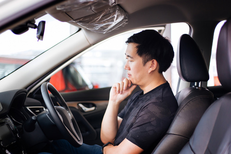 Photo pour Young Asian man as a customer sitting inside a car thinking and considering to buy automobile or car insurance - image libre de droit