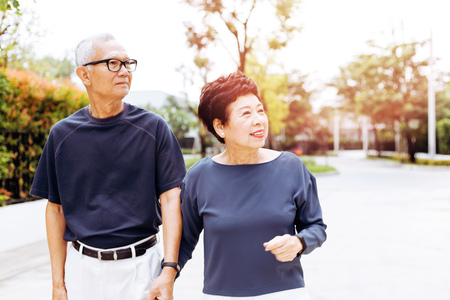 Photo pour Senior Asian couple walking in the park of residential house. Warm tone with sunlight - image libre de droit