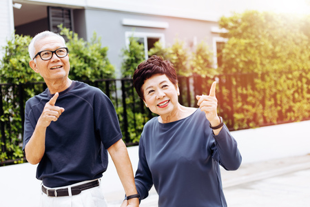 Foto de Happy senior Asian couple walking and pointing in outdoor park and house. Warm tone with sunlight - Imagen libre de derechos