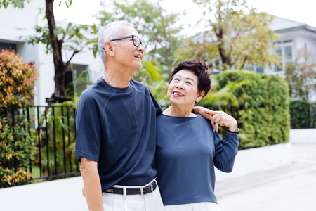 Photo for Happy retired senior Asian couple walking and looking at each other with romance in outdoor park and house in background - Royalty Free Image