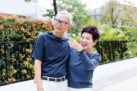 Photo for Happy senior Asian couple walking and pointing in outdoor park and house - Royalty Free Image