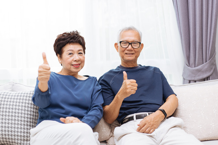 Photo for Senior Asian couple looking at camera and giving thumbs up while sitting on sofa at home - Royalty Free Image
