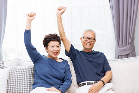 Foto de Senior Asian couple looking at camera and raising hands up while sitting on sofa at home - Imagen libre de derechos
