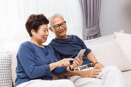 Photo pour Senior Asian couple grandparents using a smart phone together on sofa at home - image libre de droit