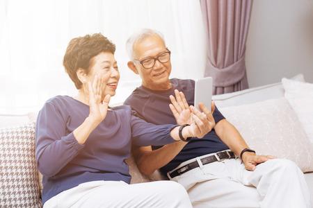 Photo pour Senior Asian couple grand parents making a video call and waving at the caller - image libre de droit