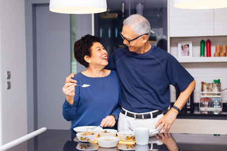 Photo pour Senior Asian couple grandparents cooking together while woman is feeding food to man at the kitchen. Long lasting relationship concept - image libre de droit