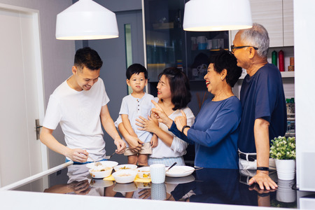 Photo pour Happy Asian extended family preparing food at home full of laughter and happiness - image libre de droit