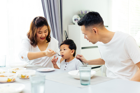 Photo for Asian parents feeding their child and the whole family having meal together at home - Royalty Free Image