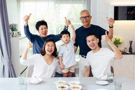 Foto de Extended Asian family of three generations having a meal together and showing thumbs up at home with happiness - Imagen libre de derechos
