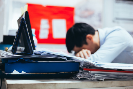 Foto de Stressful and frustrated young Asian business office worker having overwork problem crisis with tons of paperwork load - Imagen libre de derechos
