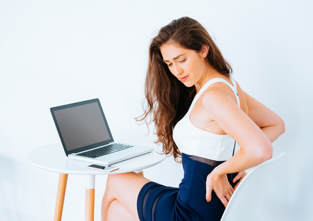 Foto de Young Caucasian working business woman on desk with laptop suffering lower back and hip pain as result from office syndrome - Imagen libre de derechos