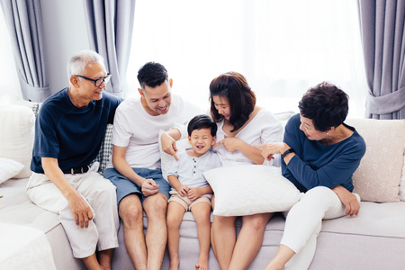 Photo pour Happy Asian extended family sitting on sofa together, posing for group photos - image libre de droit