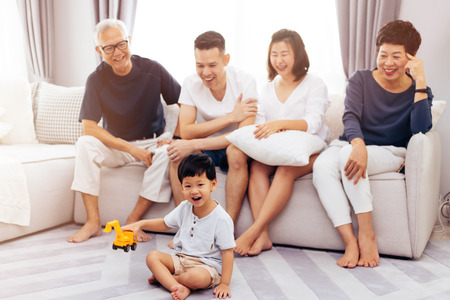 Foto de Happy Asian extended family sitting on sofa together and watching little child playing toy on the floor with happiness - Imagen libre de derechos