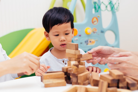 Foto de Asian child playing with wooden blocks in the room at home. A kind of educational toys for preschool and kindergarten kids - Imagen libre de derechos