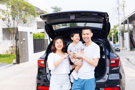 Photo pour Happy Asian family standing on the back of SUV car with smile and happiness - image libre de droit