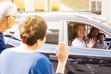 Foto de Asian family of father, mother and son waving goodbye to grandfather and grandmother as they take off their journey - Imagen libre de derechos