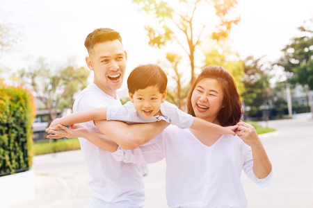 Photo for Asian family having fun and carrying a child in public park - Royalty Free Image