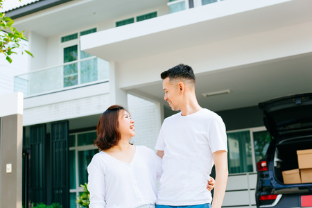 Photo for Asian couple standing in front of their new house. Newlyweds family just moved in new home and car carrying boxes - Royalty Free Image