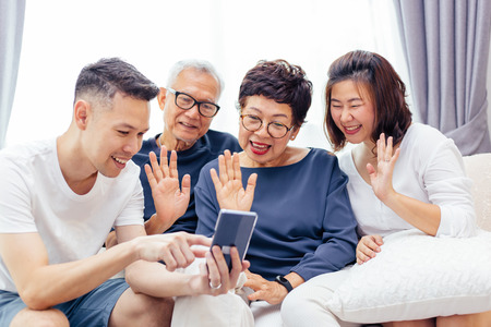 Foto de Asian family with adult children and senior parents making a video call and waving at the caller - Imagen libre de derechos