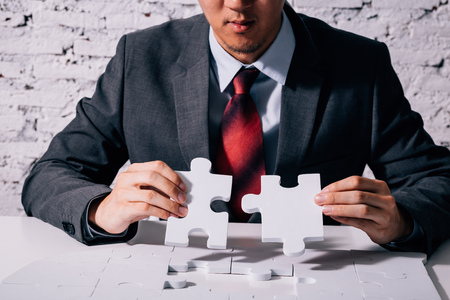 Photo pour Hands of business man working on finishing last missing pieces of jigsaw on the white desk - critical thinking and problem solving business concept - image libre de droit