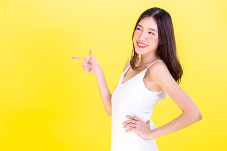 Foto de Asian cute woman pointing hands to  empty copy space and posing arms akimbo isolated on yellow background - Imagen libre de derechos