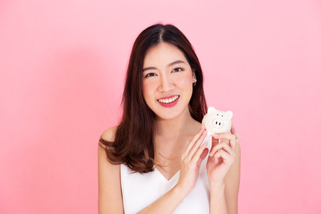 Photo pour Portrait of young Asian woman holding a piggy bank, happy and excited over own saving isolated over vivid pink background - image libre de droit
