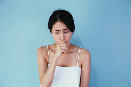 Photo pour Young Asian woman suffering from cough / lung or throat problems isolated over blue background - Healthcare and Medical concept - image libre de droit