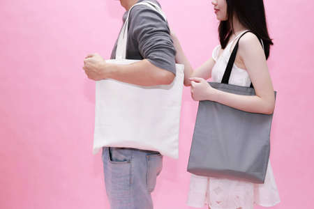 Photo pour Young male and female couple using an empty blank tote cotton bag together in pink background - with copy space to insert anything - image libre de droit