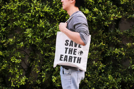 Foto de Young male hipster holding and carrying the Save The Earth tote handbag in green nature environment background - ecology and recycle concept - Imagen libre de derechos