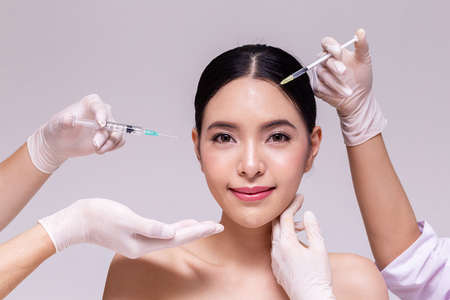 Photo pour Mixed Asian young 20s woman going through skin care and aesthetic medical therapy and to be injected by hands of doctor with syringes in white background - image libre de droit