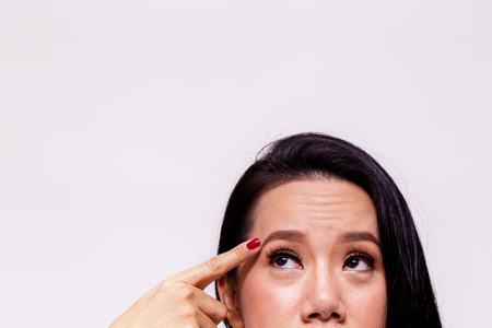 Photo pour Asian young woman worried and pointing finger towards her aging and old forehead - with copy space - treatment skin care concept - image libre de droit