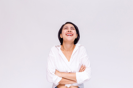 Foto de Young beautiful and confident Asian girl with short hair arms crossed with joy and happiness in white isolated background - Imagen libre de derechos