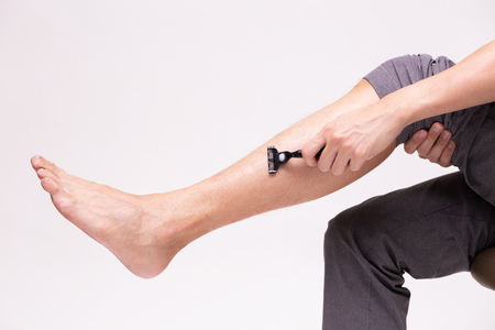 Foto de Part of human legs going to shave and remove leg hair with shaving razor in white isolated background - Imagen libre de derechos