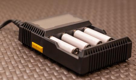 Foto de Stack of rechargeable AA batteries being recharged - Close up shot - Imagen libre de derechos