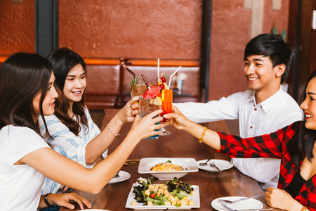 Photo pour Group of Asian happy and smiling young man and women holding an alcoholic cocktail for toasting and celebrating in social party in restaurant - image libre de droit