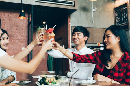 Foto de Group of Asian happy and smiling young man and women holding an alcoholic cocktail for toasting and celebrating in social party in restaurant - Imagen libre de derechos