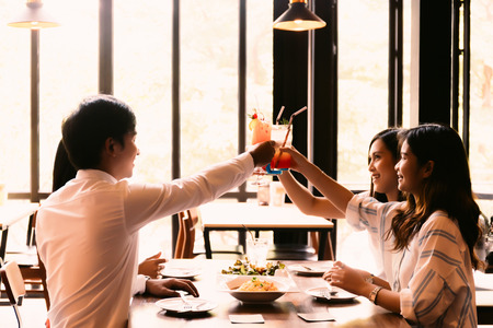 Photo pour Group of Asian happy and smiling young man and women holding an alcoholic cocktail for toasting in restaurant against sunset - image libre de droit