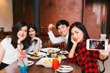 Foto de Group of Happy Asian male and female friends taking a selfie photo and having a social toast together in restaurant - Imagen libre de derechos